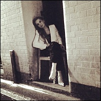 Lindsay Lohan - Sitting on a chair in a door way holding a lit cigarette LYP.jpg